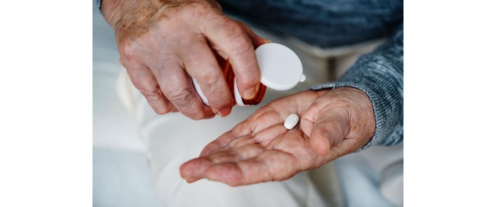 personne agée montrant un médicament dans sa main