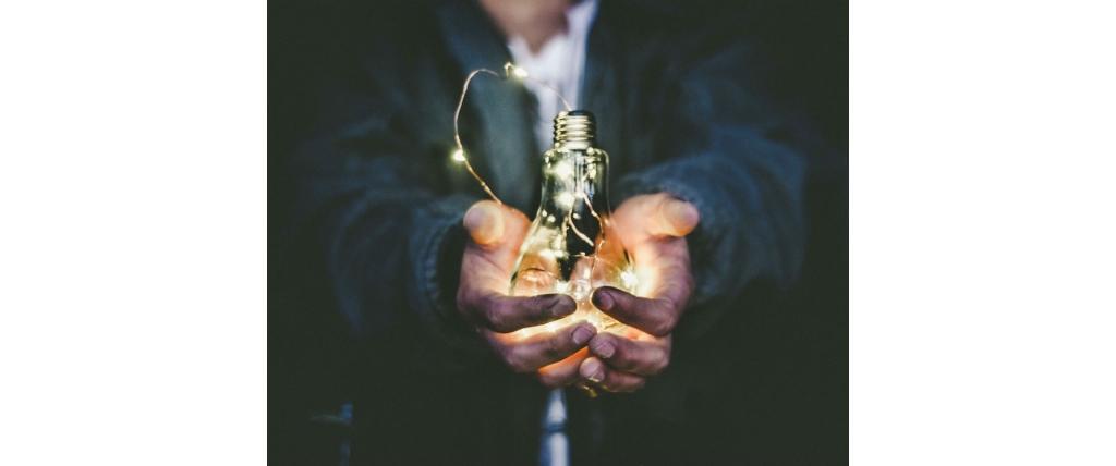 homme tenant une ampoule allumée dans ses mains