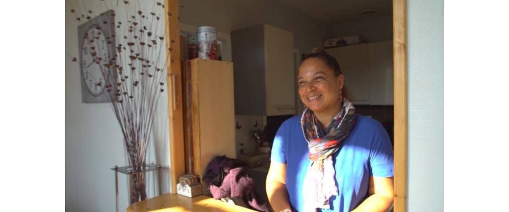 femme assise à une table et qui sourit